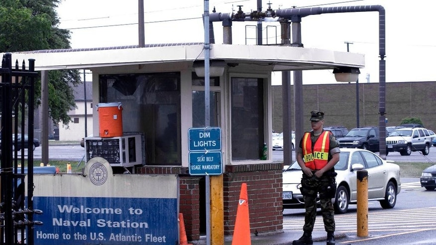 In this May 3, 2004 file photo, security personnel wait to inspect vehicles entering Norfolk Naval Station in Norfolk, Va. A sailor was fatally shot at the world's largest naval base late Monday, March 24, 2014, and security forces killed a male civilian suspect, base spokeswoman Terri Davis said.