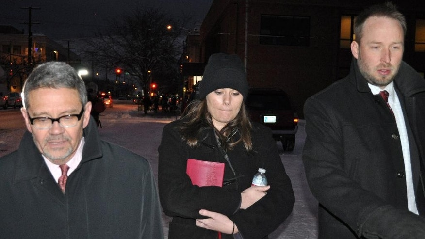 FILE - In this Tuesday, Dec. 10, 2013 file photo, Jordan Graham, center, is flanked by defense attorneys Michael Donahoe, left, and Andy Nelson, as she leaves court in Missoula, Mont. The Montana woman who was to be sentenced Thursday for pushing her new husband to his death in Glacier National Park wants to withdraw her guilty plea to a second-degree murder charge, her lawyer said Tuesday March 25, 2014.  (AP Photo/Stephan Ferry, File)