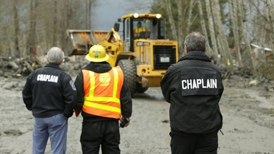 March 25, 2014: Washington State Patrol chaplains Joel Smith, left, and Mike Neil, right, watch as workers using heavy equipment work to clear debris from Washington Highway 530 on the western edge of the massive mudslide that struck near Arlington, Wash. Saturday, killing at least 16 people and leaving dozens missing. (AP Photo/Ted S. Warren, Pool)