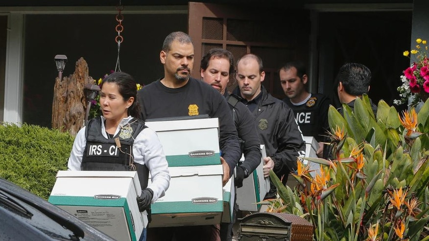 Agents from the FBI and the IRS carry boxes from a home in San Mateo, Calif., on Wednesday, March 26, 2014.  FBI Agent Greg Wuthrich said the raid was part of an investigation involving the arrest of State Sen. Leland Yee early Wednesday morning. (AP Photo/San Jose Mercury News, John Green)  MAGS OUT; NO SALES