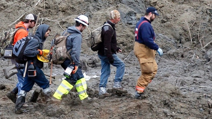 March 26, 2014: Searchers walk into the scene of a deadly mudslide that covers the road in Oso, Wash. Sixteen bodies have been recovered, but authorities believe at least 24 people were killed.