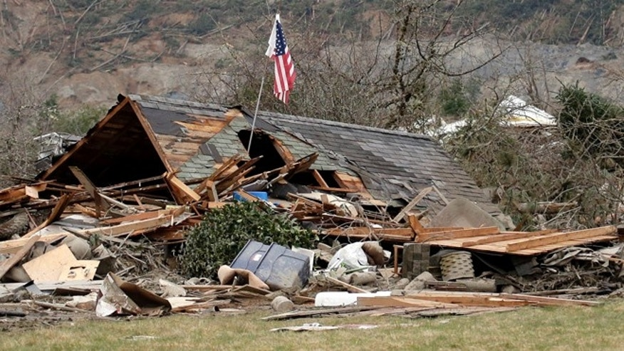 March 25, 2014: A flag, put up by volunteers helping search the area, stands in the ruins of a home left at the end of a deadly mudslide from the now-barren hillside seen about a mile behind in Oso, Wash.