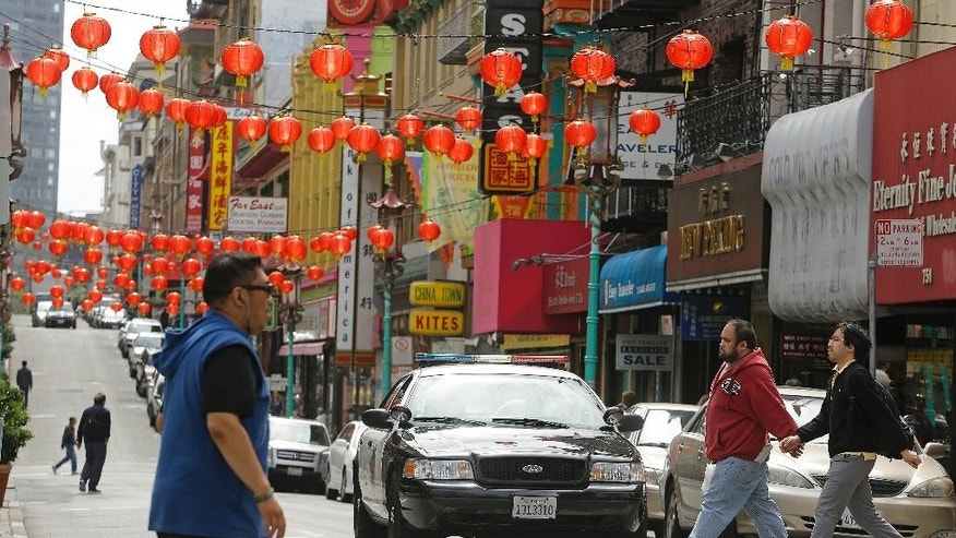 San Francisco police patrol the Chinatown district Thursday, March 27, 2014, in San Francisco. Beneath the strings of red paper lanterns and narrow alleyways of the nation's oldest Chinatown lies an underworld, a place with a history of opium dens, gambling houses and gangland murders.  (AP Photo/Ben Margot)