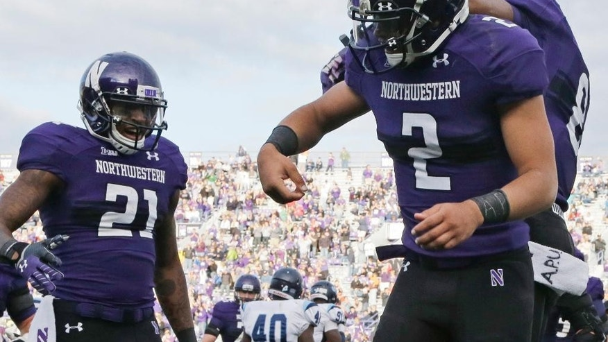 "FILE - In this Sept. 21, 2013 file photo,  Northwestern quarterback Kain Colter (2) wears APU for ""All Players United"" on wrist tape while celebrates with running back Stephen Buckley (8) and wide receiver Kyle Prater (21) after scoring a touchdown in an NCAA college football game against Maine in Evanston, Ill.  The decision to allow Northwestern football players to unionize raises an array of questions for college sports. Among them, state schools vs. public schools, powerhouse programs vs. smaller colleges. (AP Photo/Nam Y. Huh, File)"