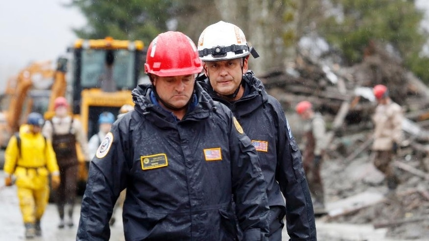FEMA wooers head out of the site of a deadly mudslide, Friday, March 28, 2014, in Oso, Wash. Besides the 26 bodies already found, dozens more people could be buried in the debris pile left from the mudslide nearly one week ago. (AP Photo/Lindsey Wasson, Pool)