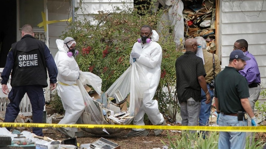 Hazardous materials contractors for the city remove debris from the home where a body was found in the 6200 block of Martel Avenue in Dallas, Texas on Thursday, March 27, 2014. Dallas fire and police departments started searching the house following a welfare check on Saturday. Due to the circumstances the City Attorney's office was contacted to obtain a warrant to provide a removal process of the debris from inside the home.  A contractor was secured to begin the removal process. On Thursday the contractors reported that they had found a dead body inside the home.  (AP Photo/The Dallas Morning News, Brad Loper)