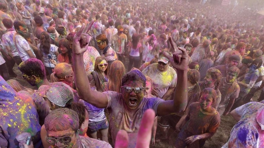 Revelers covered in colored corn starch celebrate during the 2014 Festival of Colors, Holi Celebration at the Krishna Temple Saturday, March 29, 2014, in Spanish Fork, Utah. Nearly 70,000 people are expected to gather starting Saturday at a Sri Sri Radha Krishna Temple in Spanish Fork for the annual two-day festival of colors. Revelers gyrate to music and partake in yoga during the all-day festival, throwing colored corn starch in the air once every hour. The Salt Lake Tribune reports that the large majority of participants are not Hindus, but Mormons. Thousands of students from nearby Brigham Young University come to take part in a festival that is drug and alcohol free. The event stems from a Hindu tradition celebrating the end of winter and the triumph of good over evil. (AP Photo/Rick Bowmer)