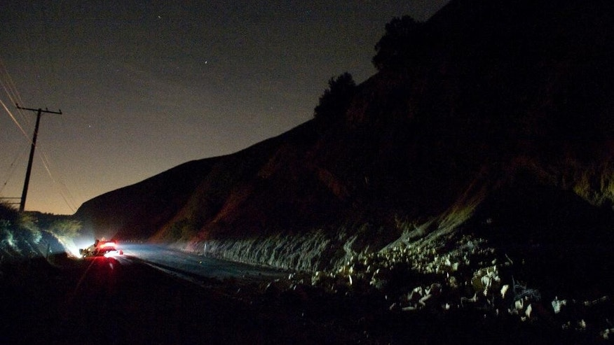 A car sits rolled over near a rockslide, right, in the wake of Friday nights March 28, 2014 earthquake on Carbon Canyon Road in Brea, Calif., near Olinda Village. (AP Photo/The Orange County Register, Rod Veal)