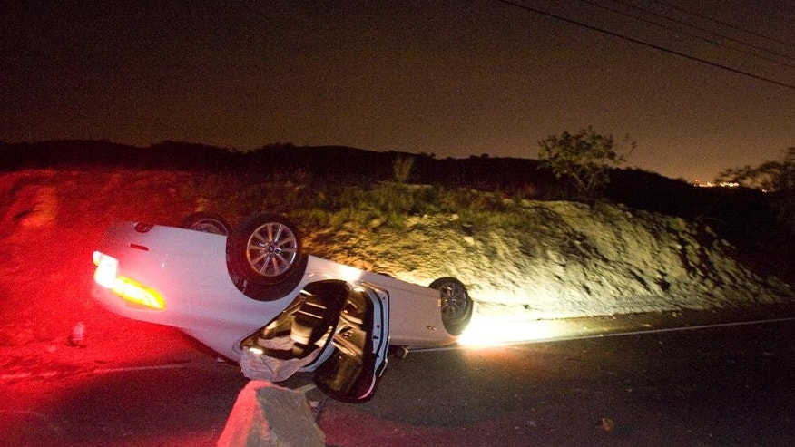 A car sits rolled over in the wake of Friday nights March 28, 2014 earthquake on Carbon Canyon Road in Brea, Calif., near Olinda Village. (AP Photo/The Orange County Register, Rod Veal)