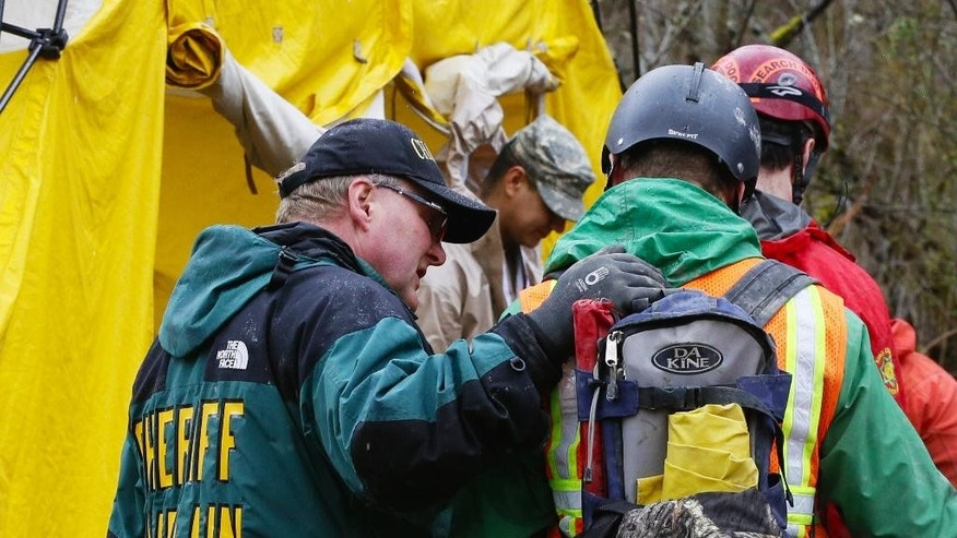 A sheriff chaplain offers a few words to a rescue worker as he enters the decontamination tent area at the west side of the mudslide on Highway 530 near mile marker 37  in Arlington, Wash., on Sunday, March 30, 2014. Periods of rain and wind have hampered efforts the past two days, with some rain showers continuing today. Last night, the confirmed fatalities list was updated to 18, with the number of those missing falling from 90 to 30. (AP Photo/Rick Wilking, Pool)