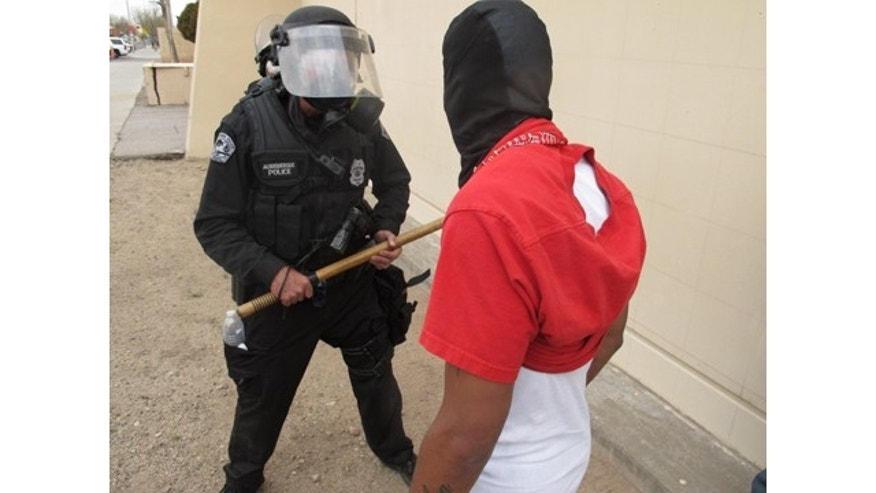March 30, 2014: A protester faces off with an Albuquerque officer during a rally against recent police shootings in Albuquerque, N.M. Hundreds of protesters marched past riot police in Albuquerque on Sunday, days after a YouTube video emerged threatening retaliation for a recent deadly police shooting. The video, which bore the logo of the computer hacking collective Anonymous, warned of a cyberattack on city websites and called for the protest march. (AP Photo/Russell Contreras)