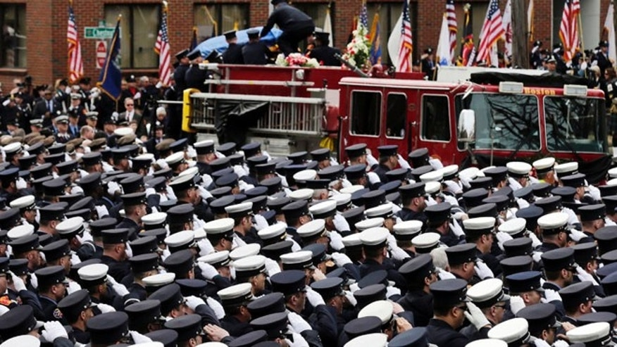 April 2: Firefighters salute as the casket of Boston fire Lt. Edward Walsh is lowered from Engine 33 as the funeral procession arrives outside St. Patrick's Church in Watertown, Mass.