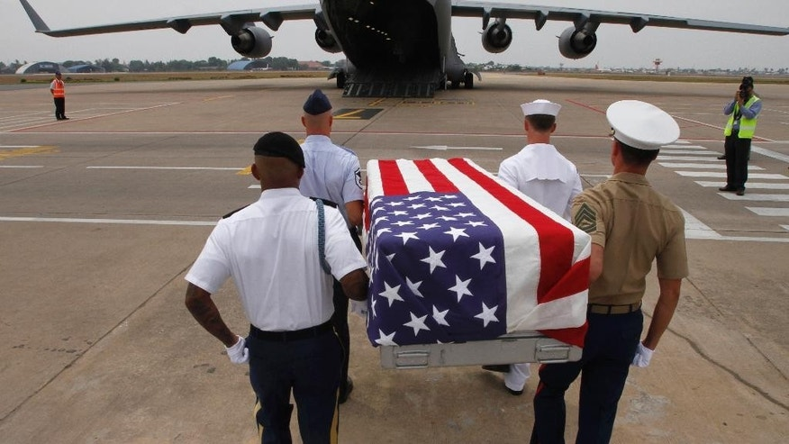 Four U.S. servicemen carry a coffin draped with the U.S. flag containing possible remains of a U.S. serviceman to a C-17 cargo plane during a repatriation ceremony at Phnom Penh International Airport, Cambodia, Wednesday, April 2, 2014. The possible remains of U.S. soldiers found in eastern Kampong Cham province were repatriated to Hawaii for testing. (AP Photo/Heng Sinith)