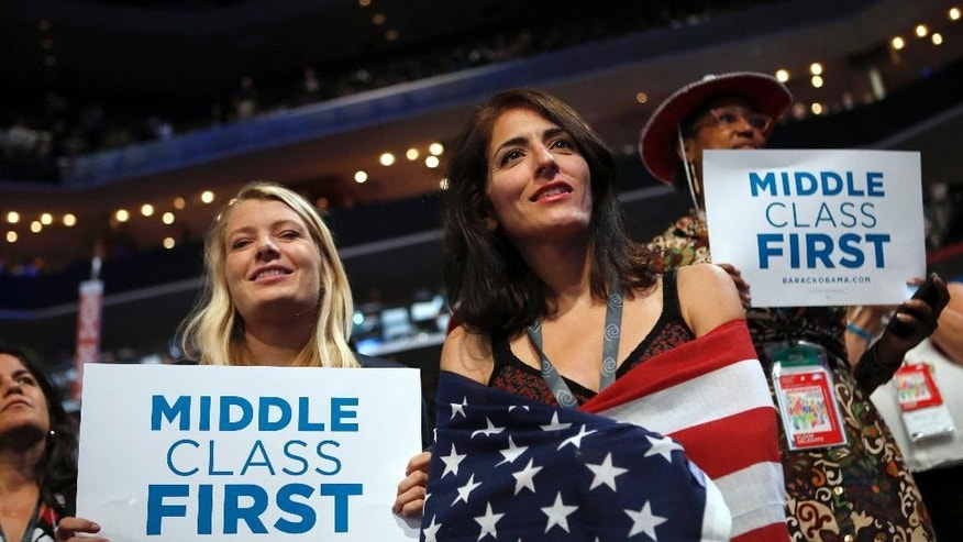 FILE - In this Sept. 5, 2012, file photo, delegates watch as former President Bill Clinton addresses the Democratic National Convention in Charlotte, N.C. Since 2008, the number of people who call themselves middle class has fallen by a fifth, according to a survey in January 2014 by the Pew Research Center, from 53 percent to 44 percent. (AP Photo/Jae C. Hong, File)