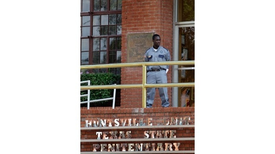 FILE - In this Sept. 21, 2011, file photo, a corrections officer keeps watch outside the Texas Department of Criminal Justice Huntsville Unit in Huntsville, Texas.  (AP Photo/David J. Phillip, File)