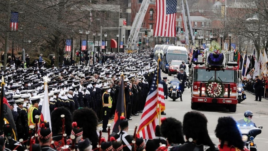 Firefighters salute as the funeral procession for Boston fire Lt. Edward Walsh arrives outside St. Patrick's Church in Watertown, Mass., Wednesday, April 2, 2014. Walsh and his colleague Michael Kennedy died after being trapped while battling a nine-alarm apartment fire in Boston on March 26. (AP Photo/Charles Krupa)