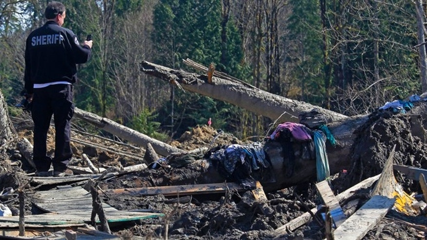April 1, 2014: A sheriff official takes photos of debris from a massive fatal mudslide near Oso, Wash. The March 22 mudslide destroyed a  rural mountainside community northeast of Seattle.