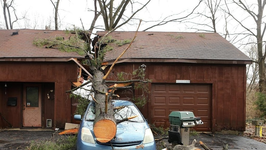 A strong storm sent a tree through his home and garage, landing on a car on Thursday, April 3, 2014 in Belleville, Ill.  Portions of southern Illinois are being told to brace for a second round of potentially volatile storms after a possible tornado hit neighboring Missouri. The National Weather Service says the storm that swept across the St. Louis region Thursday morning caused no injuries or significant damage in the metropolitan area's Illinois suburbs. (AP Photo/St. Louis Post-Dispatch, Stephanie S. Cordle)  EDWARDSVILLE INTELLIGENCER OUT; THE ALTON TELEGRAPH OUT