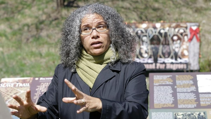 Ana Edwards, the chief opponent of the Shockoe Bottom stadium proposal gestures as she stands in front of historical markers at the Slave Burial Ground in Richmond, Va., Monday, March 31, 2014. A proposal to build a minor league baseball stadium in Shockoe Bottom, the city's oldest neighborhood and the center of the once-thriving slave trade, has drawn criticism from some who believe the area is sacred ground and shouldn't be bulldozed for a ballpark. The city says it will recover and display artifacts related to the slave trade. (AP Photo/Steve Helber)