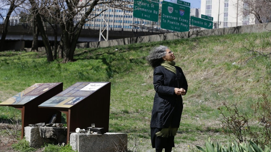 March 31, 2014: Ana Edwards, the chief opponent of the Shockoe Bottom stadium proposal looks up at some of the trees in the area in front of historical markers at the Slave Burial Ground in Richmond, Va.