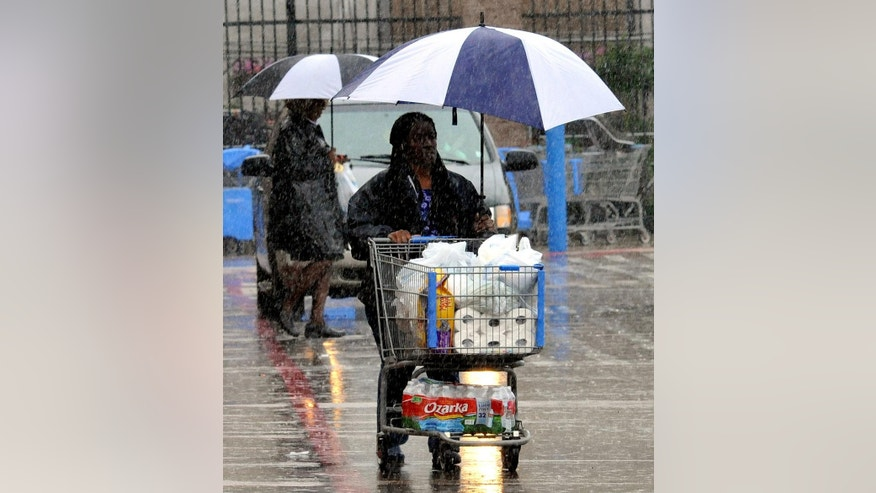 Shoppers attempt to keep dry during heavy rains on Sunday, April 6, 2014 in Ridgeland, Miss. On Sunday, street flooding plagued Jackson. Flood advisories for much of the state continued into Monday. (AP Photo/The Clarion-Ledger, Rick Guy )  NO SALES