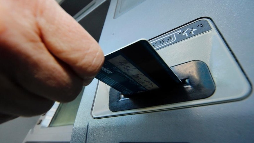 FILE - In this Saturday, Jan. 5, 2013 photo, a person demonstrates using a credit card in an ATM in Pittsburgh. The Federal Reserve on Monday, April 7, 2014 will release a report on how much consumers borrowed in February. (AP Photo/Gene J. Puskar, File)