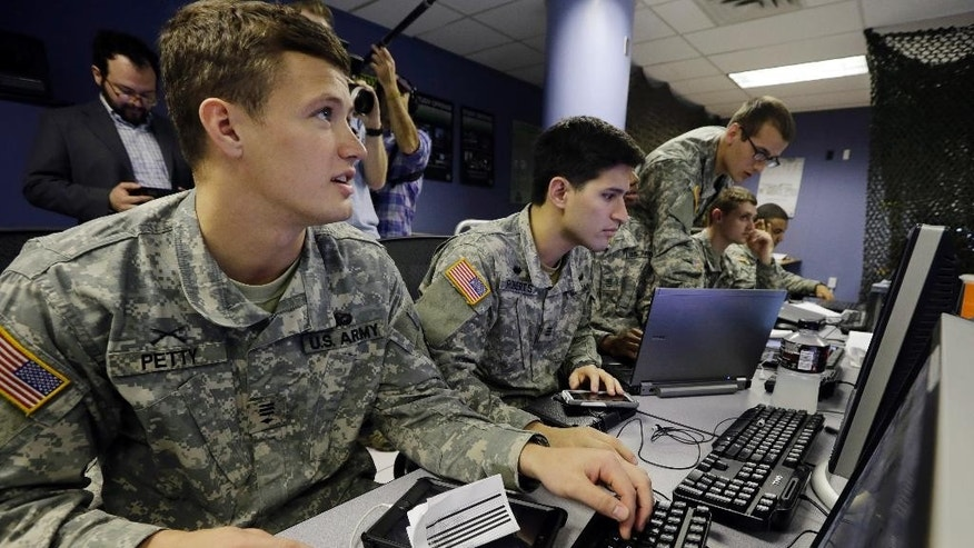 United States Military Academy cadet Brian Petty, left, watches data on a computers with, fellow cadets, at the Cyber Research Center at the United States Military Academy in West Point, N.Y., Wednesday, April 9, 2014. The West Point cadets are fending off cyber attacks this week as part of an exercise involving all the service academies. The annual Cyber Defense Exercise requires teams from the five service academies to create computer networks that can withstand attacks from the National Security Agency and the Department of Defense. (AP Photo/Mel Evans)