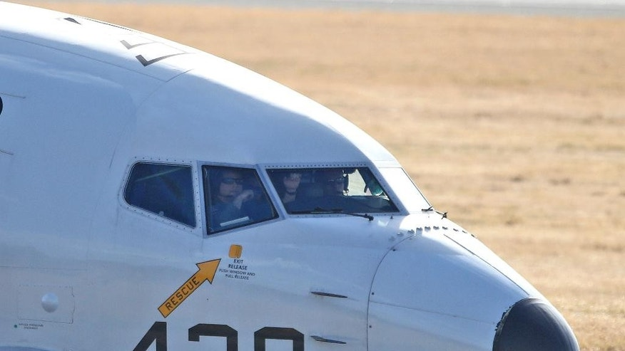 FILE - In this April 5, 2014 file photo, pilots look out of a window from the cockpit in a U.S. Navy P-8 Poseidon plane as it taxies to the end of the runway to take off from Perth Airport on route to conduct search operations for missing Malaysia Airlines Flight MH370 in southern Indian Ocean, near the coast of Western Australia. Every day from the Perth airport and a nearby military base, about a dozen planes from several countries take flight to search for debris from missing Flight 370 _ so far without success. The U.S. Defense Department alone committed $7.3 million to the effort in the first month of the search, much of it spent on two U.S. Navy P-8 Poseidon planes that cost $4,000 per hour to fly. (AP Photo/Rob Griffith, File)