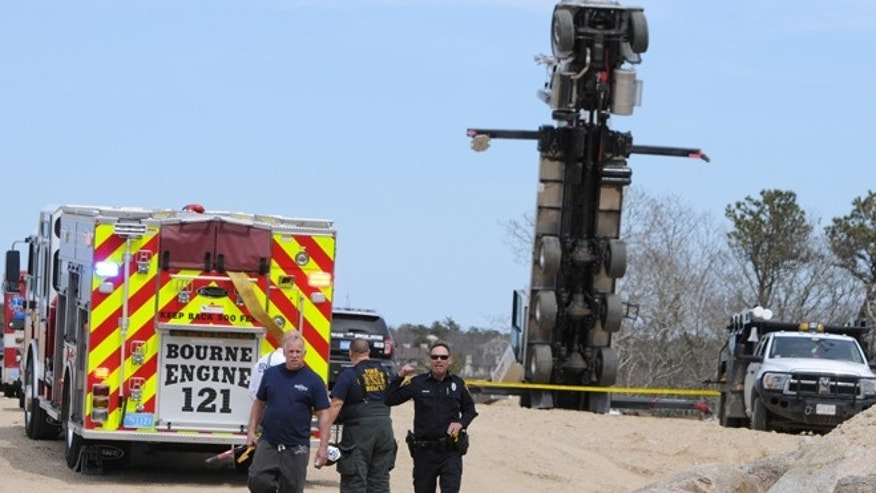 Apr. 12, 2014: Authorities work on the scene of a fatal accident where two workers died in Bourne, Mass.