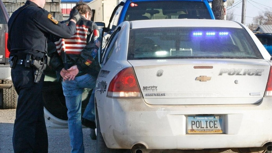 ADVANCE FOR USE SUNDAY, APRIL 13, 2014 AND THEREAFTER - An officer guides a handcuffed man into a police car in Williston, N.D. on Friday, Feb. 28, 2014. Officials at local law enforcement agencies throughout the region say a marked increase in population from the oil boom is stretching their resources. They also say crime, including drug trafficking, is up. (AP Photo/Martha Irvine)