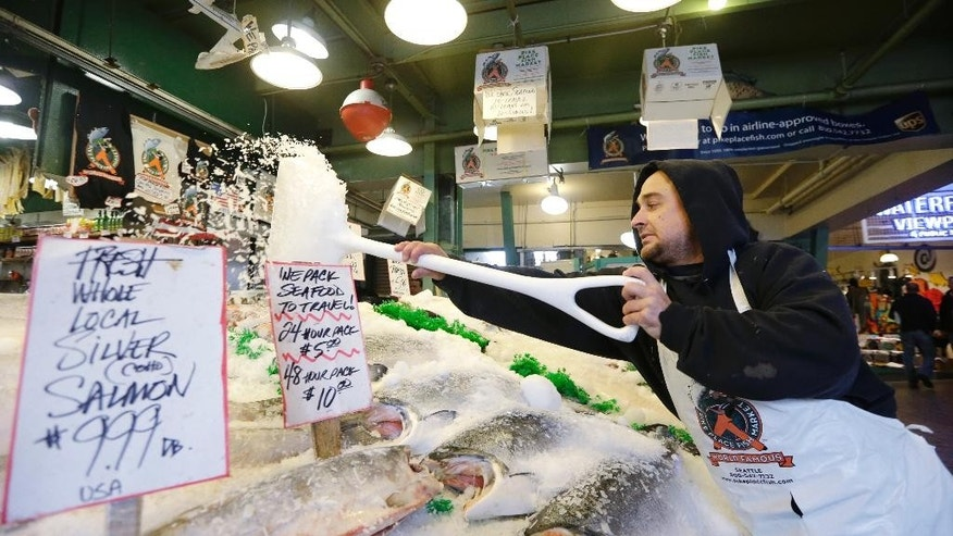 FILE - In this Oct. 3, 2013 file photo Pike Place Fish Market fishmonger Erik Espinoza shovels ice onto fresh fish at the Pike Place Market in Seattle. Lawmakers in both state legislatures and in Washington, D.C., have been considering bills that would help to ensure more accurate labeling of seafood. (AP Photo/Elaine Thompson, file)