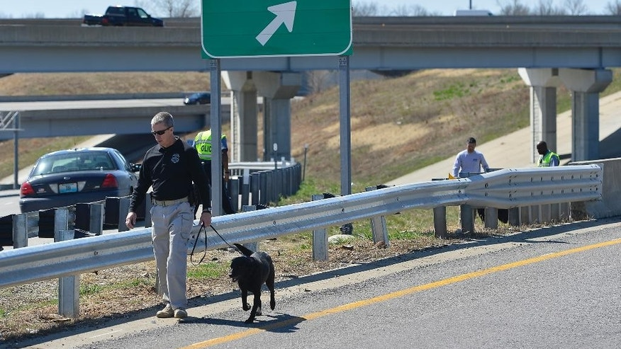 In this photo taken on Wednesday, April 9, 2014, Kansas City police and agents from the Alcohol, Tobacco and Firearms with canines investigated a shooting along southbound Interstate 435 in Kansas City, Mo. Police have connected 12 shootings targeting vehicles on Kansas City-area roads and highways since early March.  Three drivers have been wounded by gunfire, though none of the wounds was considered life-threatening. (AP Photo/The Kansas City Star, Jill Toyoshiba)