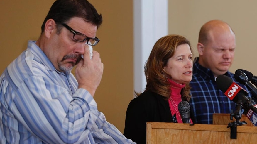 Will Corporon, left, and Tony Corporon, right, fight emotions while Mindy Losen, center, talks about her son and father during a news conference at their church in Leawood, Kan., Monday, April 14, 2014. Dr. William Corporon and his 14-year-old grandson were victims of Sunday's shooting at the Jewish Community Center. The three are sons and daughter of Dr. Corporon and Losen is the mother of the 14-year-old victim. (AP Photo/Orlin Wagner)