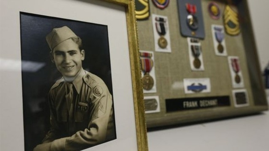 April 14, 2014: A framed photo and medals, including a Bronze Star, sit on display during a ceremony at which 91-year-old World War II veteran Frank Dechant received the United States Prisoner of War Medal, in Lakewood, Colo.