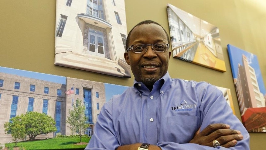 Mel Gravely, president of TriVersity Construction, poses in his office in front of some paintings of work his company has done, Wednesday, April 16, 2014, in Cincinnati. Gravely's company joined a program called a minority business accelerator even before he bought a controlling interest in the Cincinnati-based company in 2006. It helped the company get started and win contracts that have helped Triversity's revenue double. (AP Photo/Al Behrman)