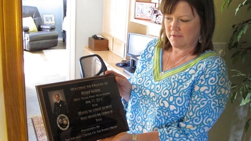 April 9, 2014: Holly Harris holds a plaque honoring her husband, Dallas Fire-Rescue Capt. Kenneth Luckey Harris, in her home outside West, Texas.