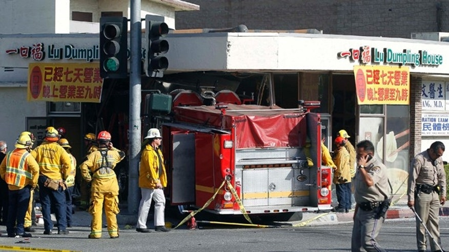 April 16, 2014: Firefighters and other officials work the scene of an accident where two firetrucks answering a call collided en route to a fire.