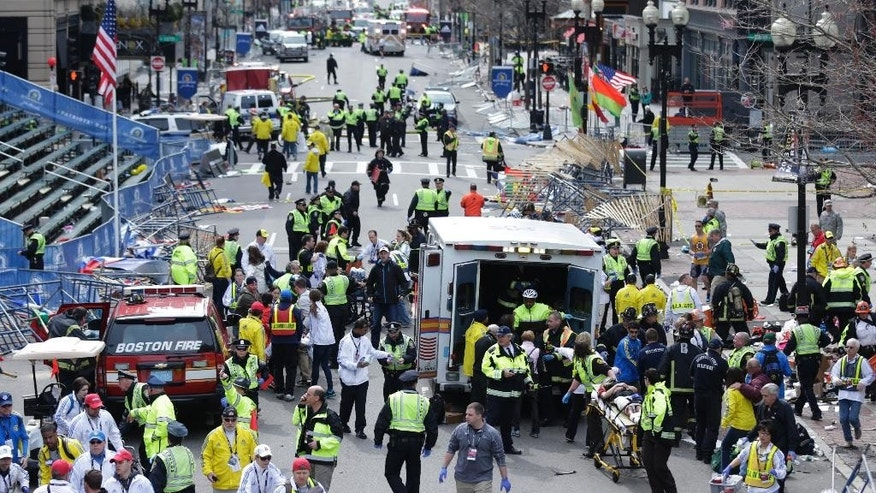 FILE - This April 15, 2013 file photo shows medical workers aid injured people following an explosion at the finish line of the 2013 Boston Marathon in Boston. In the days after the Boston Marathon bombing, the nation's political leaders pledged resources and support for a city grappling with the first terrorist attack on American soil since Sept. 11, 2001. But nearly a year after homemade bombs ripped through the marathon's finish line, there is little evidence of any lasting impact on the political world.  Federal funding that helps cities prepare for terrorism may be cut. And state and federal officials have enacted virtually no policy changes in response to the attack, a dramatic departure from previous acts of terrorism that prompted a wave of government action.  (AP Photo/Charles Krupa, File)