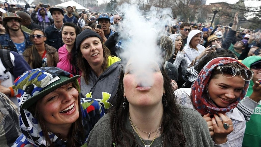 With the Colorado state capitol building visible in the background, partygoers dance and smoke pot on the first of two days at the annual 4/20 marijuana festival in Denver, Saturday April 19, 2014. The annual event is the first 420 marijuana celebration since retail marijuana stores began selling in January 2014. (AP Photo/Brennan Linsley)