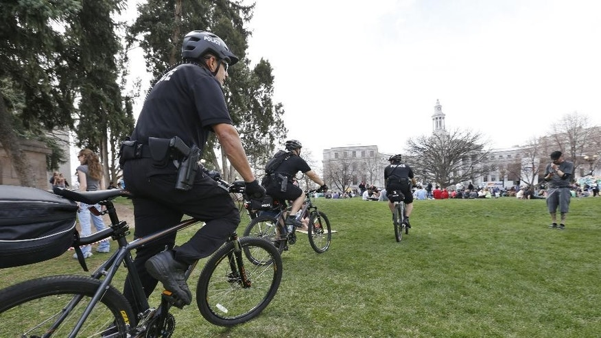 CORRECTS TO 4/20 MARIJUANA FESTIVAL -Police officers mounted on bikes patrol Civic Center Park on the first of two days at the 4/20 marijuana festival at Civic Center Park in Denver, Saturday April 19, 2014. The annual event is the first 420 marijuana celebration since retail marijuana stores began selling in January 2014. (AP Photo/Brennan Linsley)