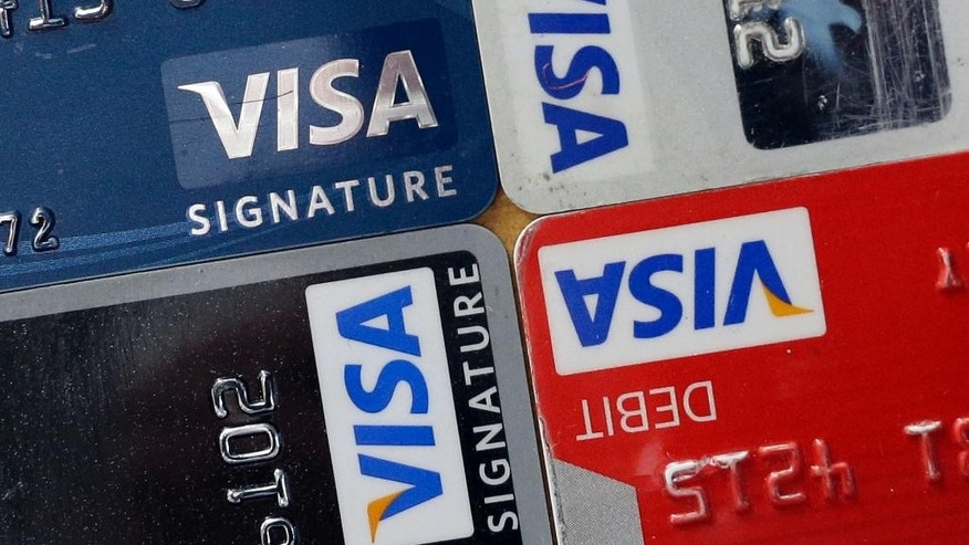 FILE - In this April 25, 2013 file photo, credit and debit cards are displayed for a photographer in Baltimore. Visa Inc. reports quarterly earnings on Thursday, April 24, 2014. (AP Photo/Patrick Semansky, File)