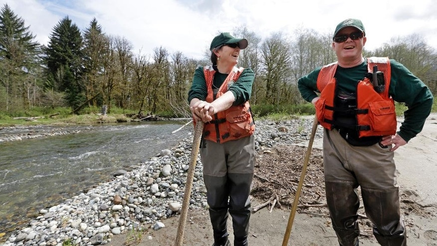 In this photo taken Tuesday, April 15, 2014, fisheries biologists Jenni Whitney, left, and Pete Verhey take a brief break after wading through Squire Creek, a tributary of the North Fork of the Stillaguamish River, while searching for salmon spawning nests near Darrington, Wash. Finding the nest, called a redd, is an encouraging sign that steelhead trout may be making their way upstream from Oso., Wash., above where a massive landslide decimated a riverside neighborhood a month ago and pushed several football fields worth of sediment down the hillside and across the river. As search crews continue to look for people missing in the slide, scientists also are closely monitoring how the slide is affecting federally endangered fish runs, including Chinook salmon and steelhead. (AP Photo/Elaine Thompson)