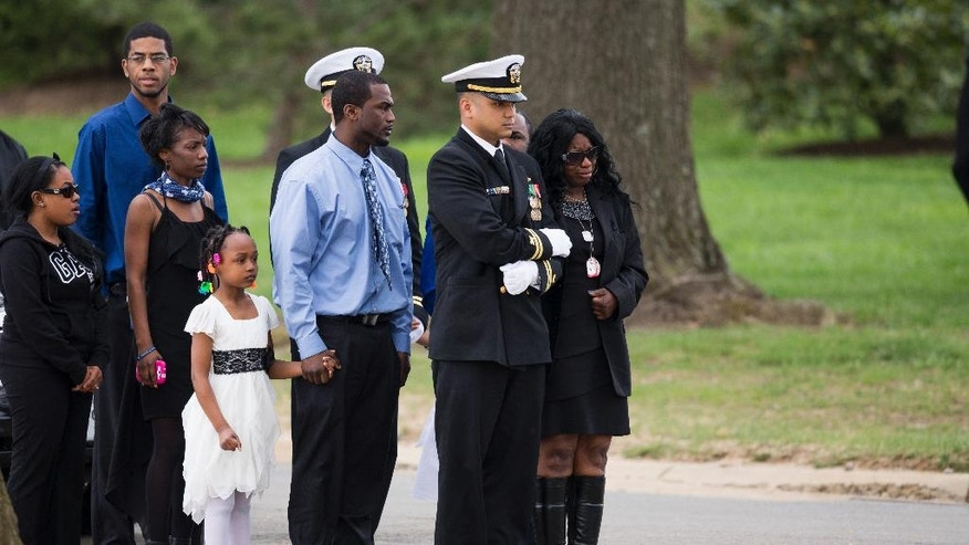 Sharon Blair, mother of U.S. Navy Petty Officer 2nd Class Mark Mayo, of Hagerstown, Md., right, waits for the arrival of her son's casket during a burial service at Arlington National Cemetery in Arlington, Va., Friday, April 25, 2014.  Mayo was killed aboard the USS Mahan at Naval Station Norfolk, Va., after he dove in front of another sailor to protect her from a civilian truck driver who had seized her gun. Mayo was awarded the Navy Marine Corps Medal, the highest non-combatant decoration for heroism by a sailor or Marine. (AP Photo/ Evan Vucci)
