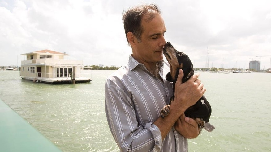 In this April 22, 2014 photo, Fane Lozman poses for photos holding his dog and in front of his home floating in the waters near North Bay Village, Fla. He caught legal lightning in a bottle last year when the U.S. Supreme Court agreed with him that his floating home was a house, not a vessel covered by maritime law. But the justices haven't had the last word: Lozman is still fighting for compensation for the home, which was destroyed years ago. The Fort Lauderdale-based federal judge whose decision on the floating home was overturned, U.S. District Judge William Dimitrouleas, refused earlier this year to give Lozman any of the $25,000 bond posted by the city of Riviera Beach to pay for Lozman's home in case he won. (AP Photo/J Pat Carter)