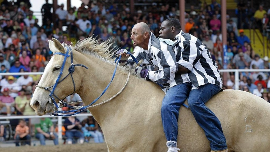 Inmates ride a horse in the Buddy Pick-Up event at the Angola Prison Rodeo in Angola, La., Saturday, April 26, 2014. Louisiana's most violent criminals, many serving life sentences for murder, are the stars of the nation's longest-running prison rodeo. In a half-century, the event has grown from a small event for prisoners into a big business that draws thousands of spectators. (AP Photo/Gerald Herbert)