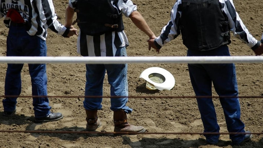 Prisoners hold hands and pray inside the ring before the start of the Angola Prison Rodeo in Angola, La., Saturday, April 26, 2014. Only the prison's most well-behaved inmates get to participate, according to the maximum-security prison's athletic director. (AP Photo/Gerald Herbert)