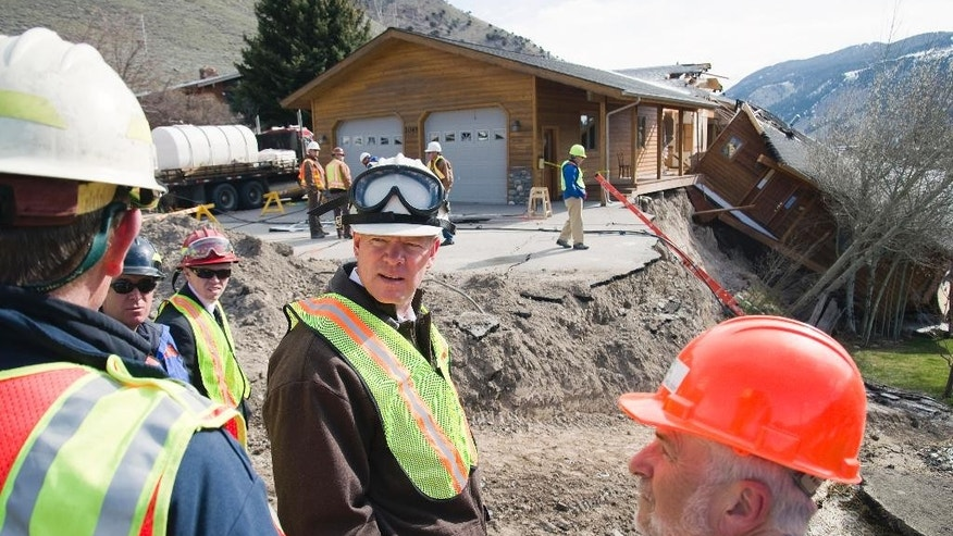 Wyoming Gov. Matt Mead, center, listens to Jackson town officials during a tour the East Gros Ventre Butte landslide Monday, April 28, 2014, in Jackson, Wyo.  Mead says after touring a slow-moving landslide he wants to help local officials defray the cost of the disaster. Efforts to slow the slide by hauling in tons of dirt and rock appear to be working. Ground movement has slowed to just a tenth of an inch per day — much less than a surge April 17 and 18 that sheared one house in two. (AP Photo/Jackson Hole News&Guide, Bradly J. Boner)