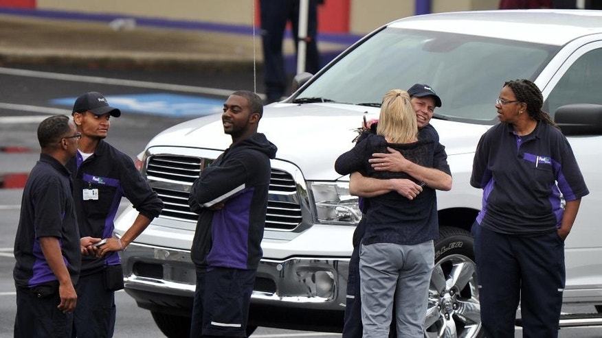 "FedEx Employees and family members gather a skating rink following a shooting at the FedEx facility in Kennesaw, Ga., on Tuesday, April 29, 2014.  A shooter described as being armed with an assault rifle and having bullets strapped across his chest ""like Rambo"" opened fire Tuesday morning at a FedEx station outside Atlanta, wounding at least six people before police found the suspect dead from an apparent self-inflicted gunshot.  (AP Photo/Atlanta Journal-Constitution, Brant Sanderlin)  MARIETTA DAILY OUT; GWINNETT DAILY POST OUT; LOCAL TV OUT; WXIA-TV OUT; WGCL-TV OUT    ."