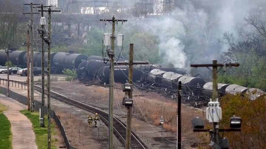 Apr. 30, 2014: Workers inspect the scene where several CSX tanker cars carrying crude oil derailed and caught fire along the James River in Lynchburg, Va.