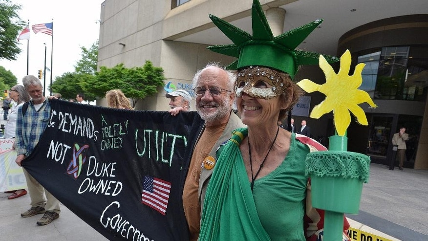 Concern citizens, Kendell Hale, dressed as Lady Liberty, and her husband Steve Norris from Asheville, N.C. demonstrate with other protesters in front of the Duke Energy office building, Thursday, May 1, 2014, as  shareholders hold their annual meeting in Charlotte, N.C. Some Duke Energy investors plan to push the utility's board of directors to investigate issues surrounding a massive coal ash spill that dumped toxic sludge into a 70-mile stretch of a North Carolina river. (AP Photo/The Charlotte Observer, T. Ortega Gaines) MAGS OUT; TV OUT; NEWSPAPER INTERNET ONLY (REV-SHARE)